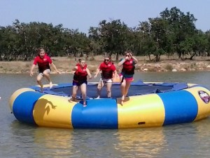 the girls jumping off the water trampoline